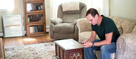 Man checking his phone while in livingroom