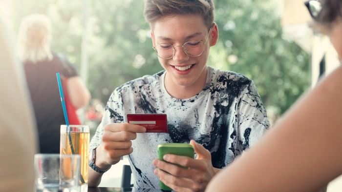 boy with glasses holding credit card