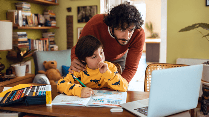 man helping his kid with the online class
